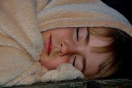 child sleeping with brown textile