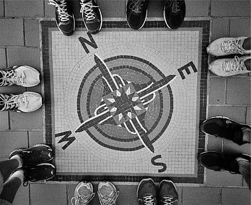 road painted with square compass surrounded by group of people wearing sneakers
