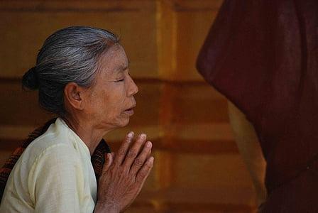 woman praying with close eyes during daytime