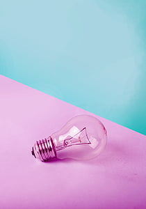 clear glass light bulb on pink table