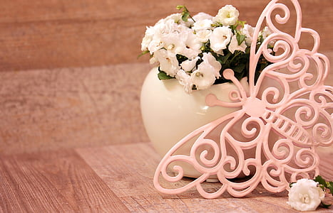pink buttery decor leaning in potted white petaled flower