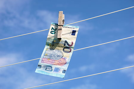 20 banknote hanging on white rope