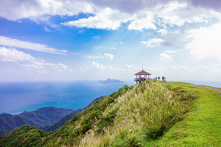 brown gazebo on top of the mountain under cloudy sky