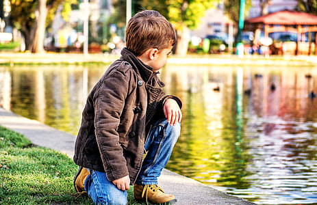 boy kneeling on green grass beside body of water at daytime