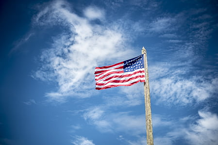 USA flag under white clouds during daytime