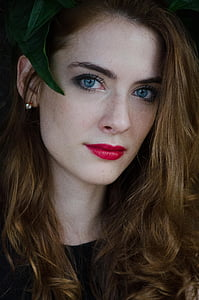 woman wearing green headdress and red lipstick