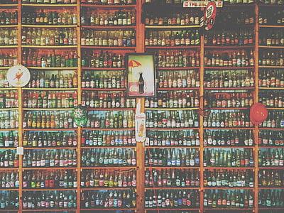 assorted-color bottle in brown rack