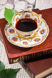 white and multicolored-print teacup with saucer