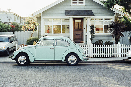 teal Volkswagen Beetle near white wooden house