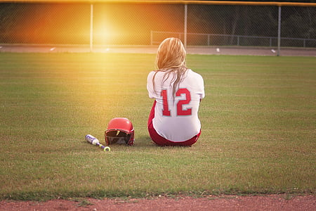 woman in white and red 12 jersey sitting on the field beside baseball bat and batting hat