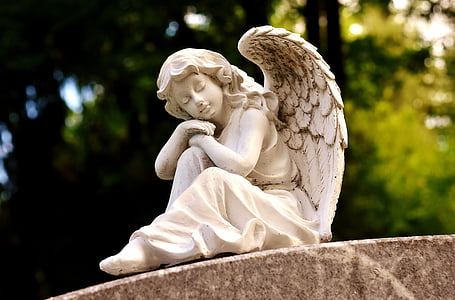 focus photography of female angel statuette