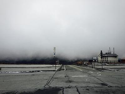 grey asphalt road under the cloudy sky