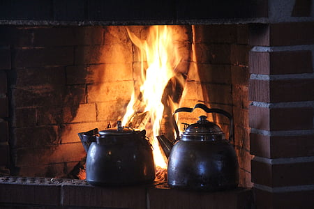 two gray kettles on brown fireplace