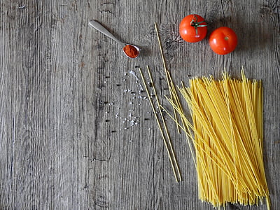 uncooked pasta and two red tomato fruits on grey wooden surface