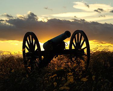 sihouette of antique cannon during sunset