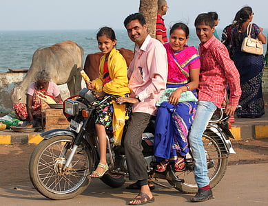 group of people riding motorcycle on road near body of water during daytime