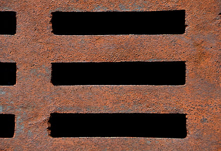 close-up photo of brown metal drainage