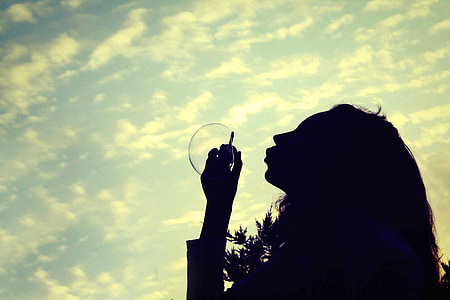 silhouette photo of woman making bubble