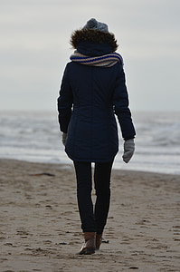 person walking on seashore