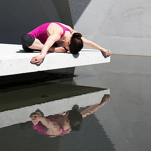 woman in purple top performing yoga