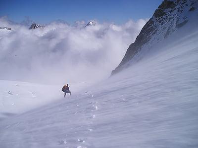 person climbing snowy mountain