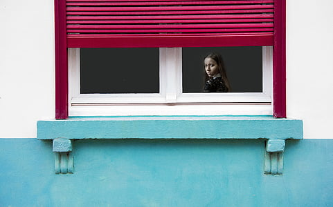 girl inside the house looking at the window during daytime