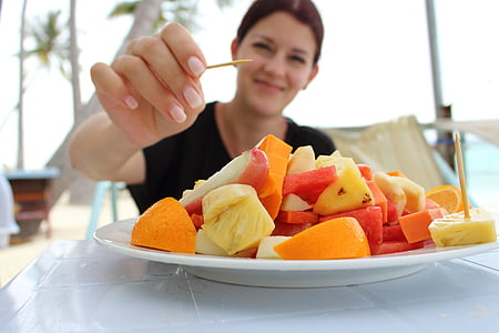 woman holding toothpick about to pick variety of sliced fruits