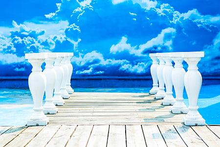 white concrete pillar near body of water