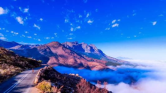 brown mountain beside white fog