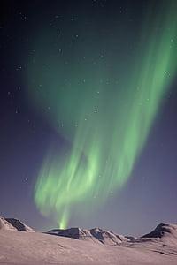 aurora borealis above gray mountains