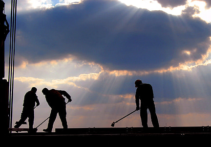men working under the cloudy sky