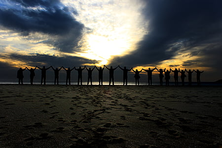 silhouette of group of people raising their hands