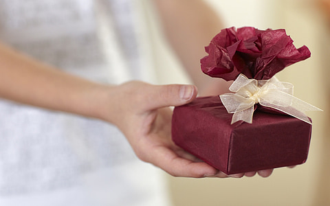 person holding maroon gift box
