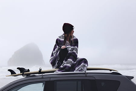 woman sitting on top of gray SUV with surfboard