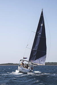 people in white and black sailboat at daytime