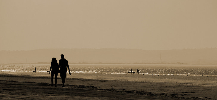 man and woman holding hands while walking near beach
