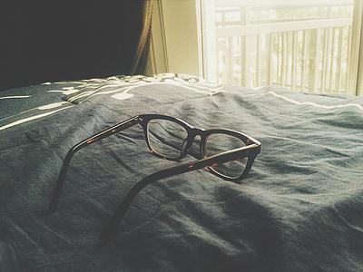 black framed eyeglasses on gray textile