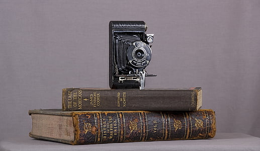 folding camera on top of brown book