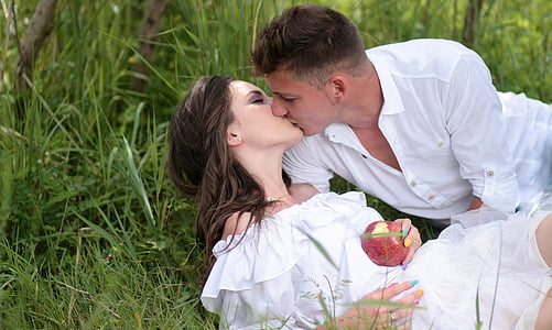 man and woman kissing while lying near green plants at daytime