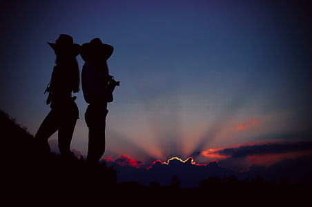 silhouette of two cowgirls standing on a cliff