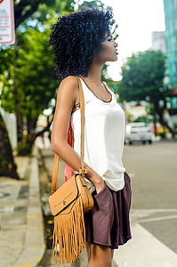 woman in white tank top with brown leather shoulder bag standing on street during daytime