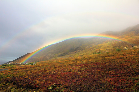 landscape photography of green mountain with rainbow