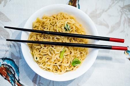 noodles in white ceramic bowl and black chopsticks