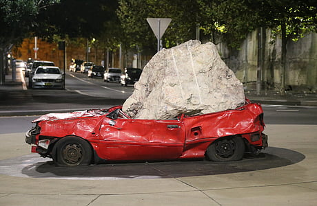 red car squashed by gray stone