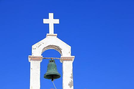 black bell mounted on cross