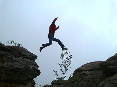 man jumping on rock