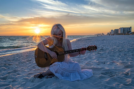 woman in white dress sitting on white sand while playing a guitar