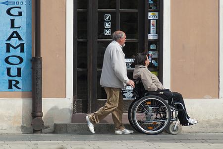 man pushing girl in wheelchair