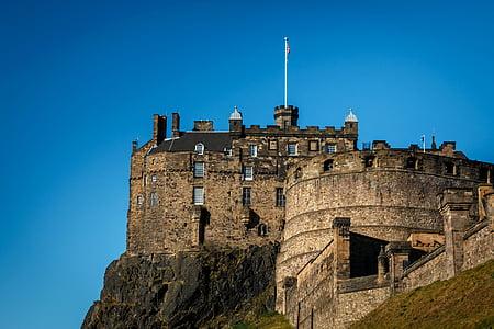 brown castle on cliff under blue sky during daytime