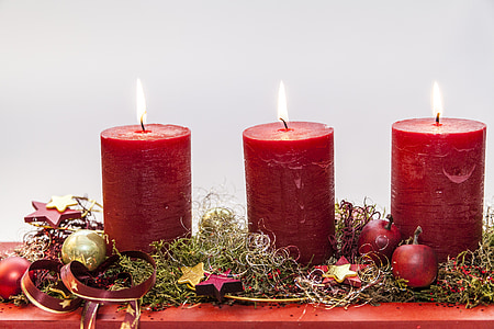 focus photo of three red lighted pillar candles
